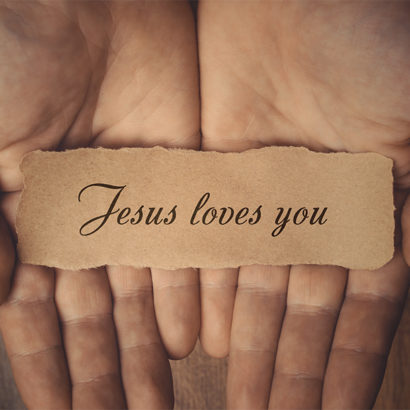Male hands holding piece of paper with inscription Jesus loves you