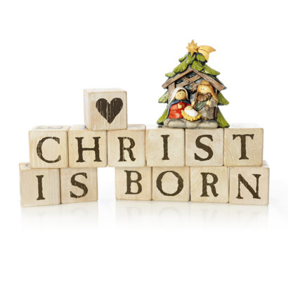 """Rustic alphabet blocks arranged to say, """"Crhist is born.""""  They're topped with a heart-block and a small nativity scene with Mary, Joseph and baby Jesus.  On a white background."""