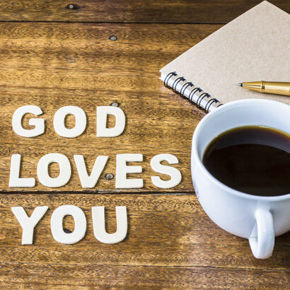 """Word """"God loves you"""" design by white letter press with a cup of coffee and small note book, pen on wooden background"""